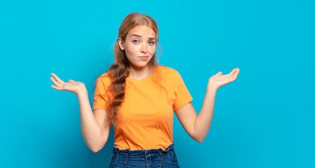 Blonde hübsche frau, die sich verwirrt und verwirrt fühlt, zweifelt, gewichtet oder verschiedene optionen mit lustigem ausdruck wählt