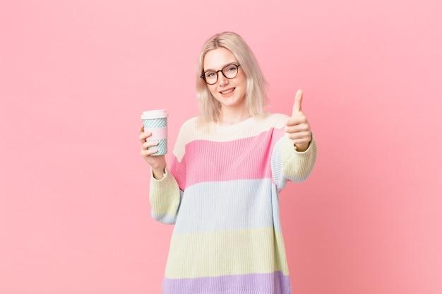 Blonde hübsche frau, die stolz ist und positiv mit daumen nach oben lächelt. kaffeekonzept