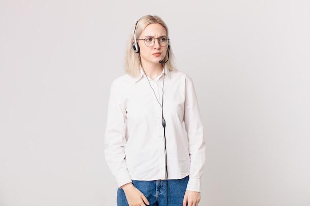 Blonde hübsche frau, die traurig, verärgert oder wütend ist und zum telefonmarketing-konzept schaut