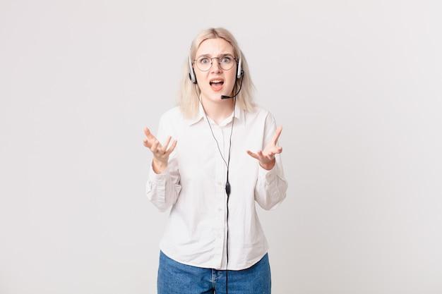 Blonde hübsche frau, die verzweifelt, frustriert und gestresstes telemarketing-konzept aussieht