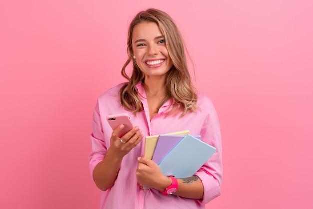 Blonde hübsche frau im rosa hemd, die lächelt, hält notizbücher in der hand und benutzt das smartphone, das auf rosa posiert