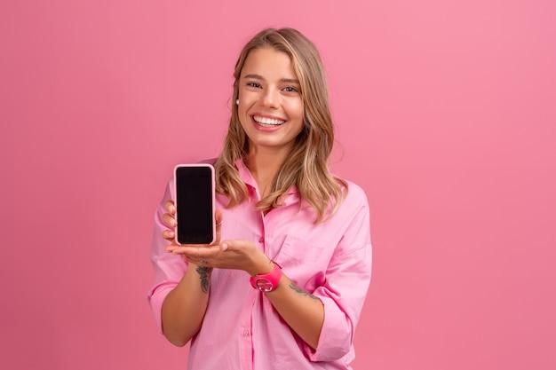 Blonde hübsche frau in rosa hemd lächelnd mit smartphone posiert auf rosa lächeln, spaß habend, telefonbildschirm zeigend
