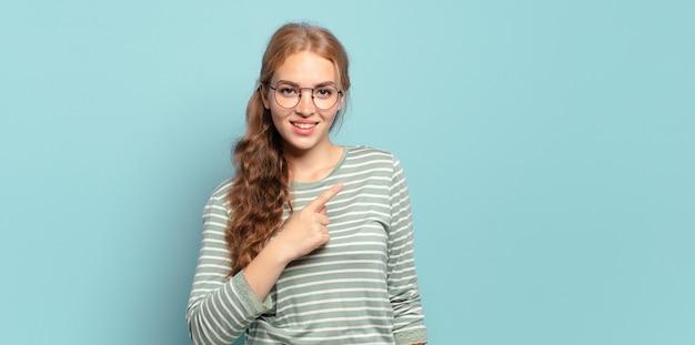 Blonde hübsche frau lächelt fröhlich, fühlt sich glücklich und zeigt zur seite und nach oben, zeigt objekt im kopierraum