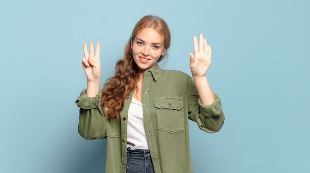Blonde hübsche frau lächelt und sieht freundlich aus, zeigt nummer acht oder acht mit der hand nach vorne, countdown