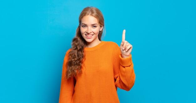 Blonde hübsche frau lächelt und sieht freundlich aus, zeigt nummer eins oder zuerst mit der hand nach vorne, countdown