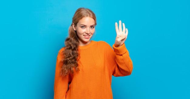 Blonde hübsche frau lächelt und sieht freundlich aus, zeigt nummer vier oder vierten mit der hand nach vorne, countdown