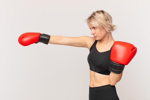 Blonde hübsche frau mit boxhandschuhen
