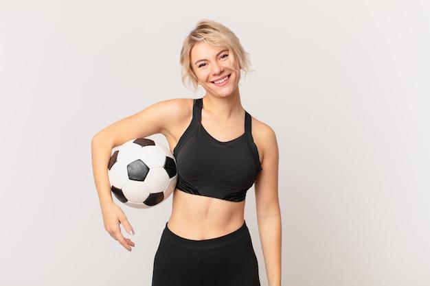 Blonde hübsche frau mit einem fußball