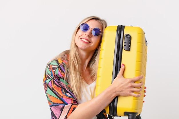 Blonde hübsche frau mit einem koffer. sommerkonzept