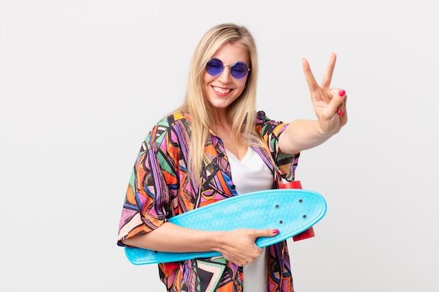 Blonde hübsche frau mit einem skateboard. sommerkonzept