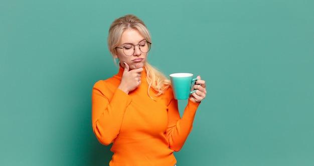 Blonde hübsche frau mit einer kaffee- oder teetasse