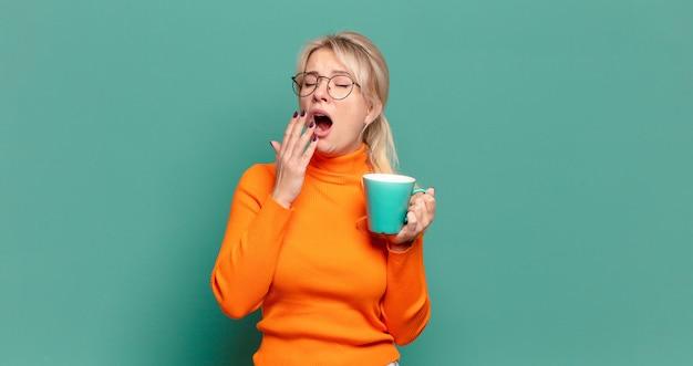 Blonde hübsche frau mit einer kaffeetasse