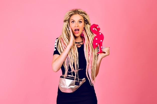 Blonde hübsche frau mit langen blonden dreads, die plastikflamingo halten, stilvolles sport-schickes outfit, überraschte emotionen, pop-last-stil tragen.