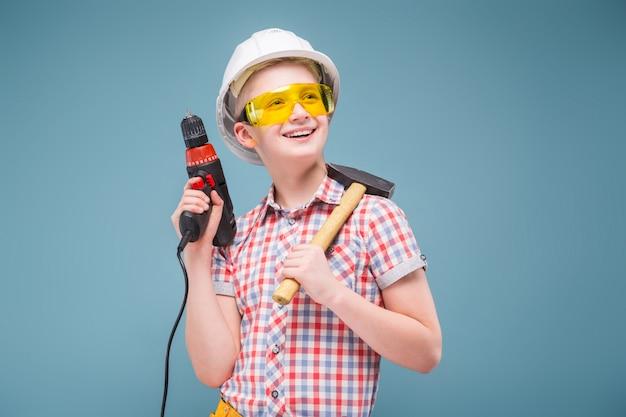Blonde jugendlichblondine im bausturzhelm mit einem schraubenzieher und einem hammer