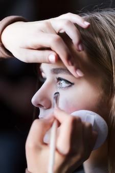 Blonde junge dame der nahaufnahme vorbereitet vom maskenbildner