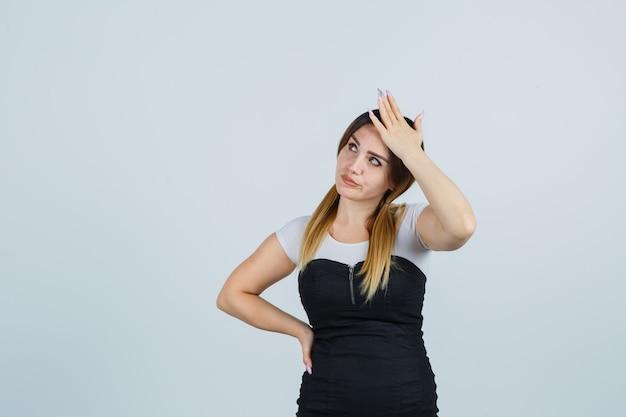 Blonde junge dame im kleid gestikuliert isoliert