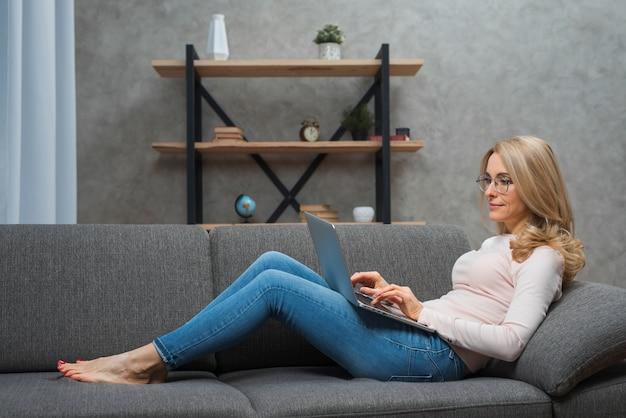 Blonde junge frau, die auf dem sofa zu hause schreibt auf laptop sitzt
