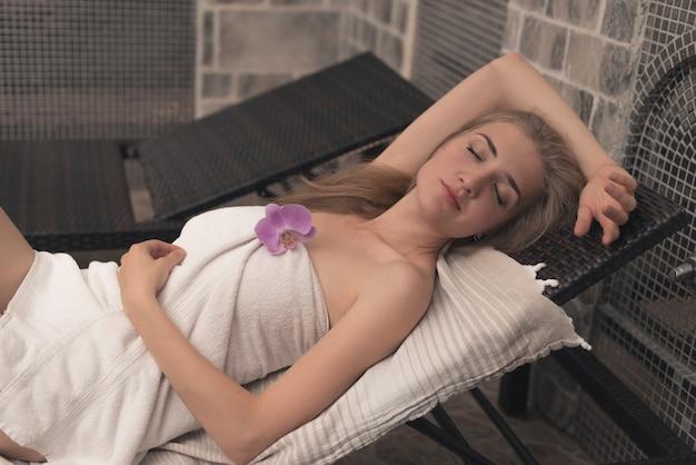 Blonde junge frau, die auf klubsessel schläft