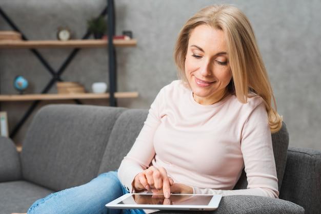 Blonde junge frau, die den digitalen tablettenschirm mit dem finger berührt