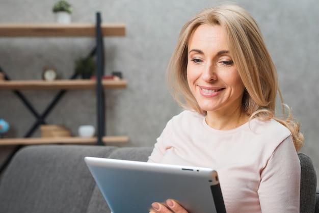 Blonde junge frau, die digitale tablette betrachtet