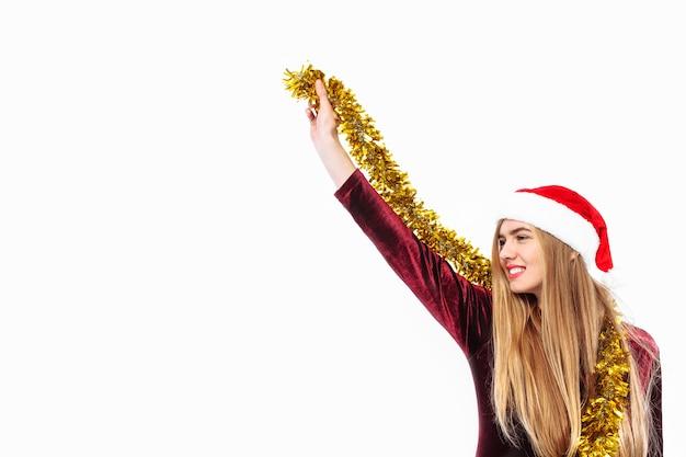 Blonde junge frau, die eine weihnachtsmannmütze und lametta trägt