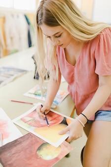 Blonde junge frau, die farbe mit farbigem bleistift auf papier gibt