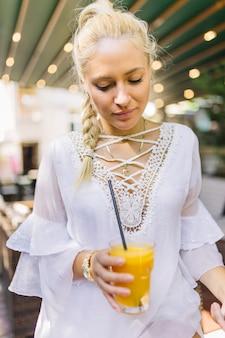 Blonde junge frau, die glas mangosaft hält