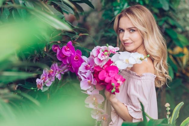 Blonde junge frau, die im garten hält orchidee steht
