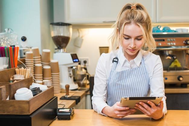Blonde junge frau, die in der kaffeestube theke betrachtet digitale tablette steht