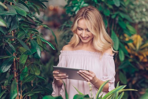Blonde junge frau, die nahe den grünpflanzen steht, betrachtend digitale tablette