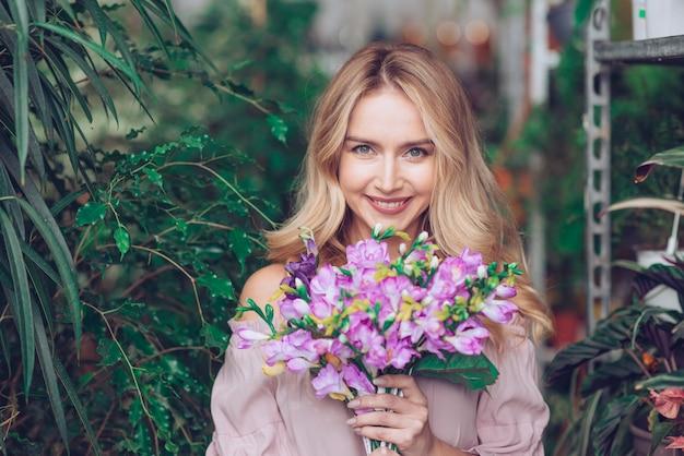Blonde junge frau, die purpurroten blumenblumenstrauß in den händen hält