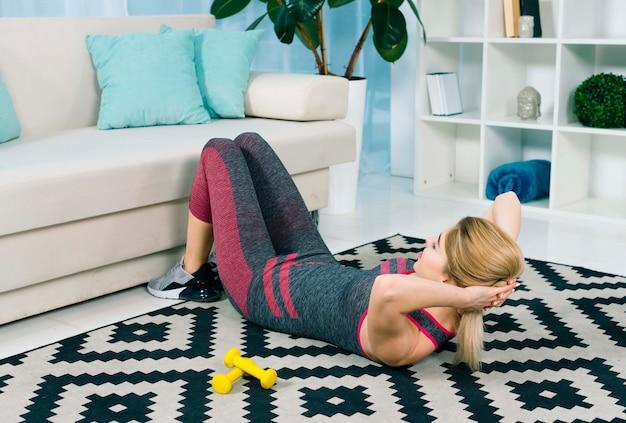 Blonde junge frau, die übung auf teppich im wohnzimmer tut