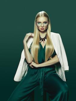 Blonde junge frau im eleganten grünen kleid.
