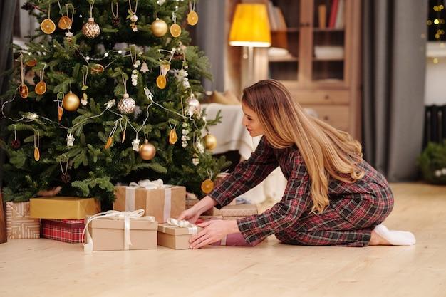 Blonde junge frau im pyjama, die verpackte geschenkboxen mit weihnachtsgeschenken unter dekorierten tannenbaum stellt, während sie eine überraschung für ihre kinder vorbereitet
