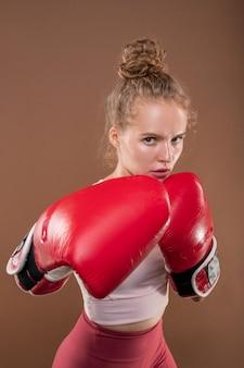 Blonde junge frau in aktivkleidung und roten boxhandschuhen