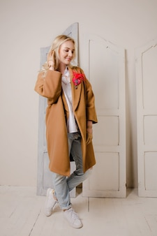 Blonde junge frau in handschuhen und mantel
