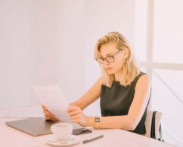 Blonde junge frau liest dokumente am arbeitsplatz im büro