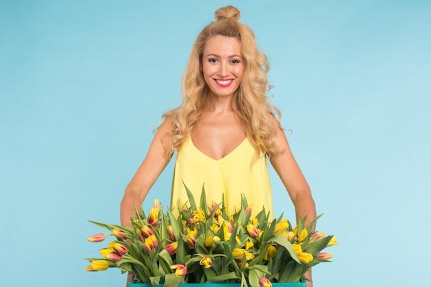 Blonde junge frau mit bündel tulpen auf blauer oberfläche