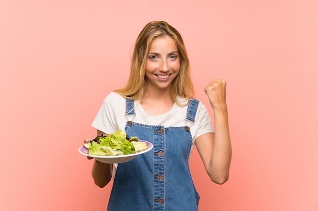 Blonde junge frau mit salat über der lokalisierten rosa wand, die einen sieg feiert