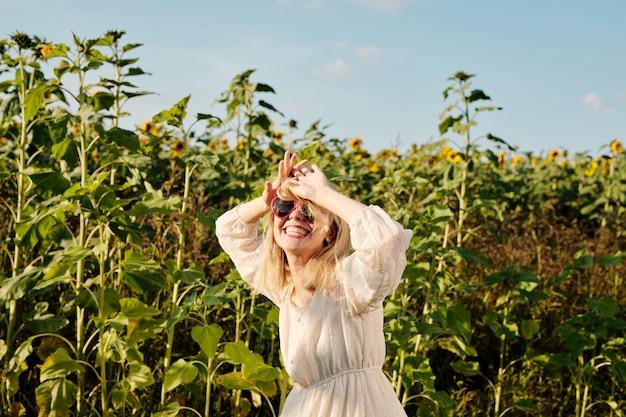 Blonde junge frau mit sonnenbrille und weißem kleid im landhausstil, die im sommer vor der kamera gegen sonnenblumenfeld und blauen himmel steht