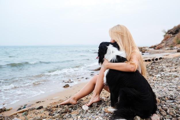 Blonde junge frau sitzt und umarmt einen hund am strand
