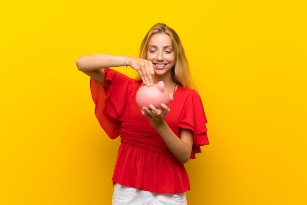 Blonde junge frau über der lokalisierten gelben wand, die ein großes sparschwein hält
