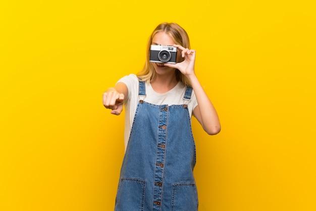 Blonde junge frau über der lokalisierten gelben wand, die eine kamera hält