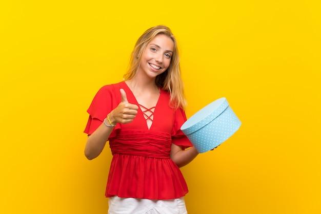 Blonde junge frau über der lokalisierten gelben wand, die geschenkbox hält