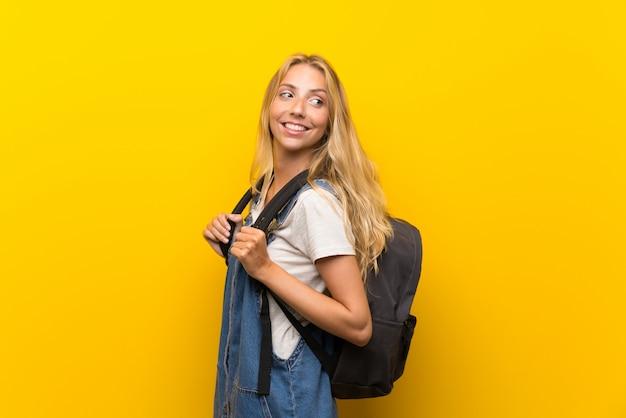 Blonde junge frau über getrennter gelber wand mit rucksack