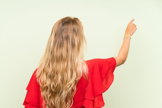 Blonde junge frau über lokalisierter grüner wand zurück zeigend mit dem zeigefinger