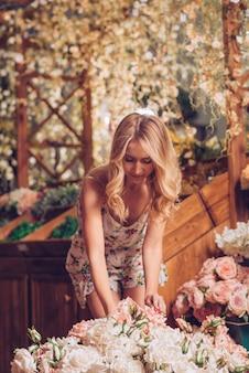 Blonde junge frau, welche die rosen im blumengarten anordnet