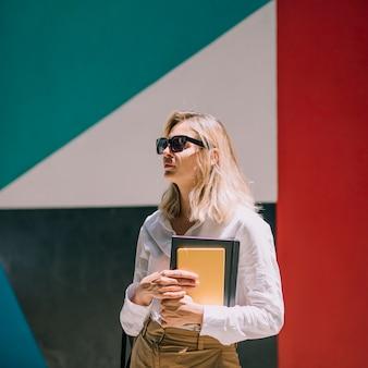 Blonde junge frau, welche die schwarzen brillen in der hand hält das buch steht vor buntem e = wall trägt