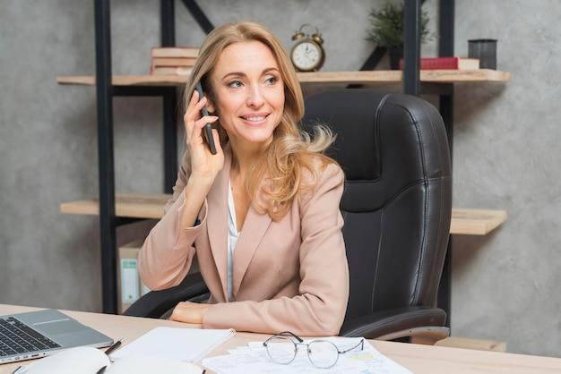 Blonde junge geschäftsfrau, die am handy sitzt auf stuhl im büro spricht