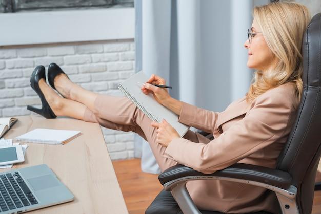 Blonde junge geschäftsfrau, die auf stuhlschreiben auf gewundenem notizbuch mit stift im büro sitzt